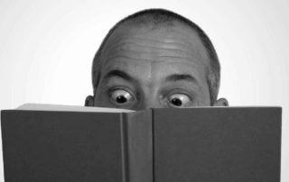 foto decorativa, homem arregalando olhos ao ler livro
