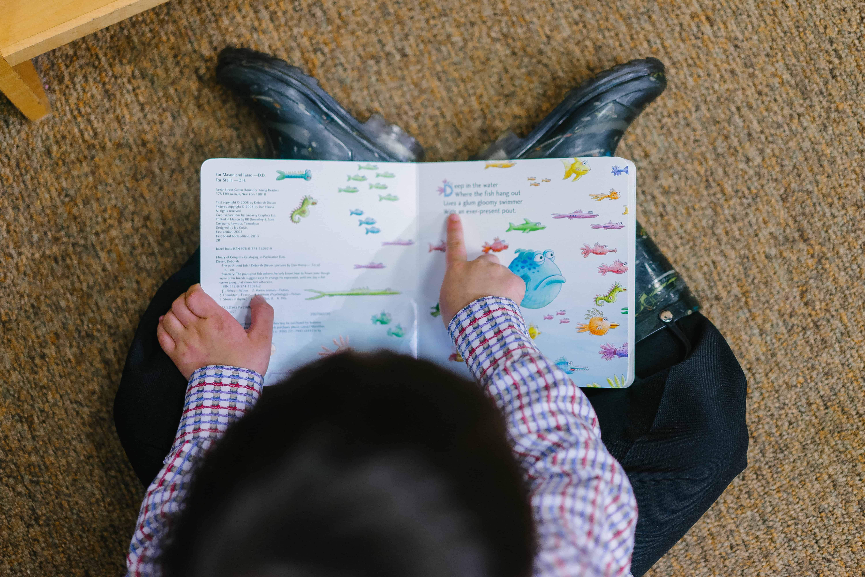 Criança lendo livro infantil